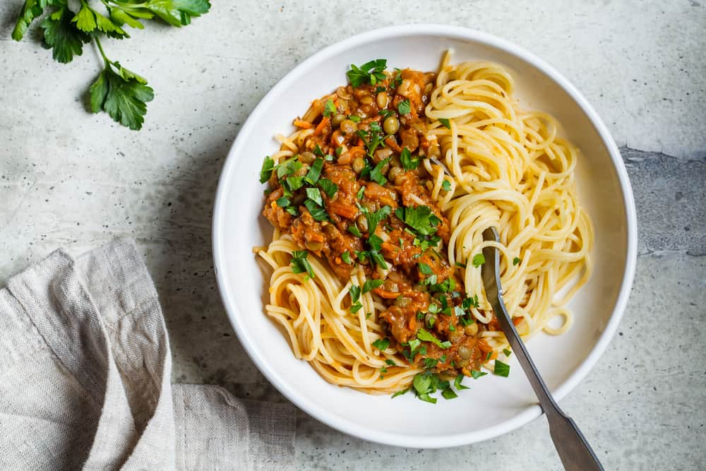 This is a fresh bowl of Lentil Bolognese pasta with parsley.