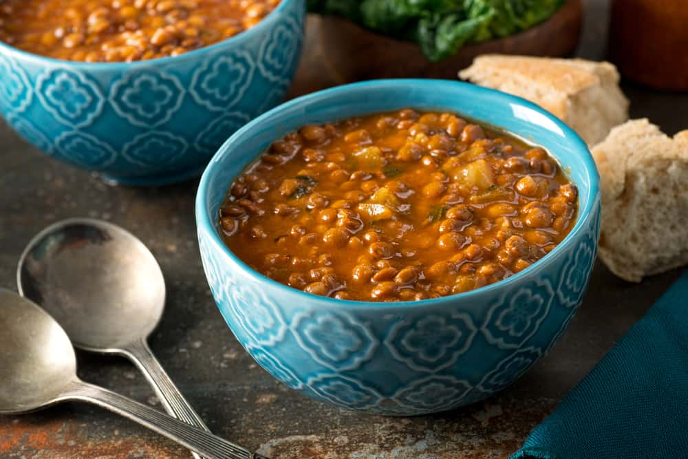 These are bowls of lentil soup with a side of bread.
