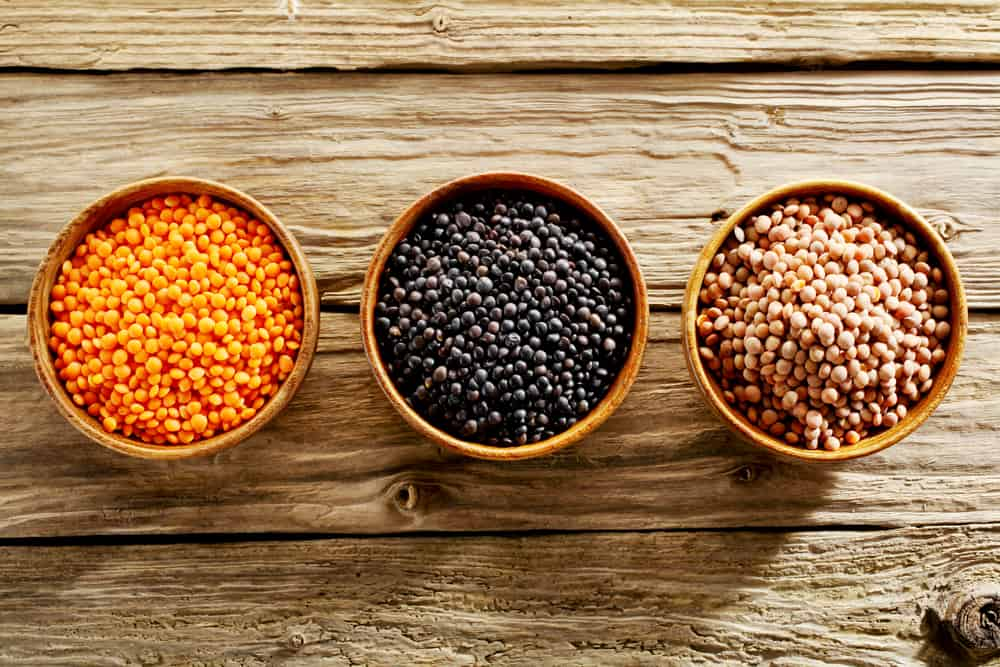This is a close look at three bowls of various types of lentils on a wooden table.