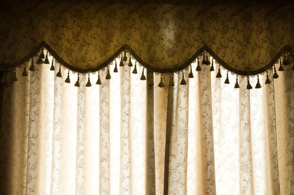 This is a close look at the home curtain with a floral pattern and a valance curtain.