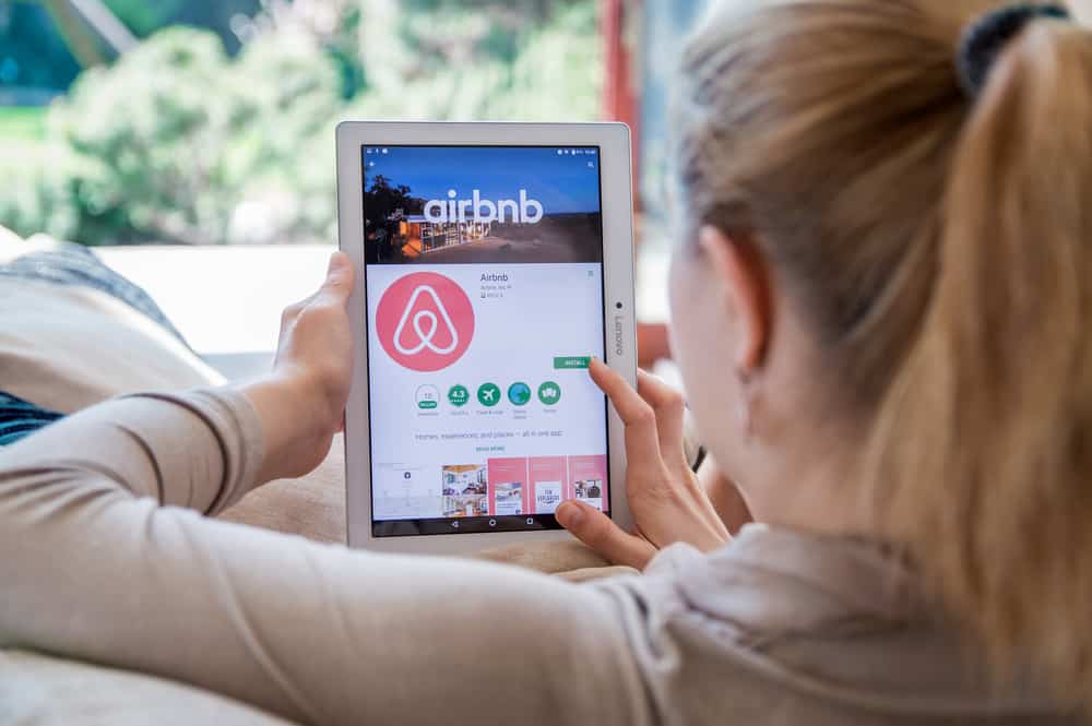 This is a woman on her tablet looking at the app installation page of Airbnb.