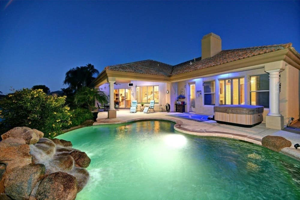 The terrace showcases multiple sitting areas, a hot tub, and a swimming pool accentuated with a stone waterfall feature.
