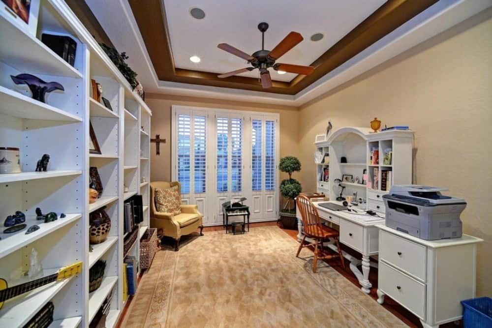 The study has a white shelving unit, a matching desk, and a tray ceiling accentuated with wooden borders.