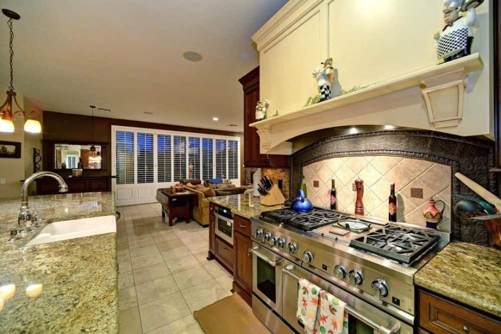 Kitchen with granite countertops, a farmhouse sink, and a double oven cooking range topped with a bespoke vent hood.