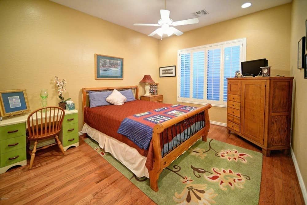 This bedroom has beige walls, a green desk, and a wooden bed that matches with the hardwood flooring topped by a floral area rug.