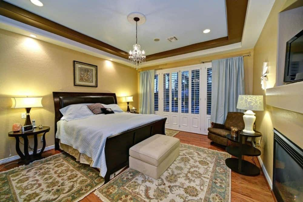 The tray ceiling is mirrored in the primary bedroom furnished with round tables, a leather recliner, and a dark wood bed complemented with a beige ottoman.