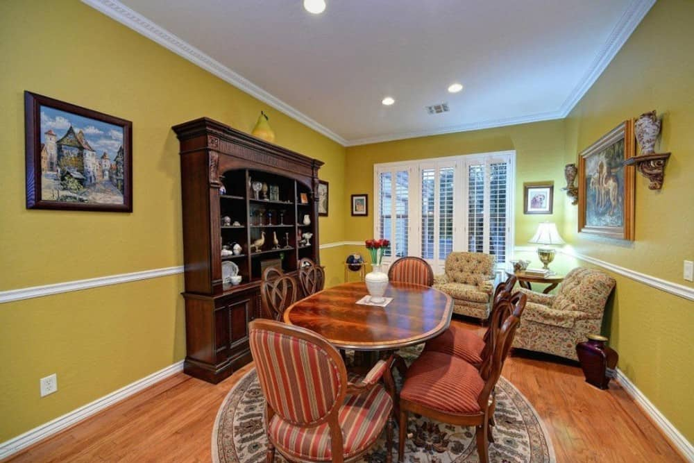 The formal dining room has an oval dining set, tufted armchairs, a wooden display cabinet, and mustard yellow walls adorned with white moldings and framed artworks.