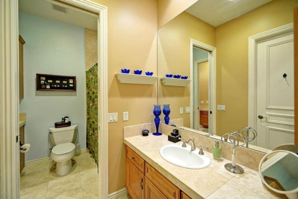 The primary bathroom is equipped with a toilet room and a large wooden vanity paired with a frameless rectangular mirror.