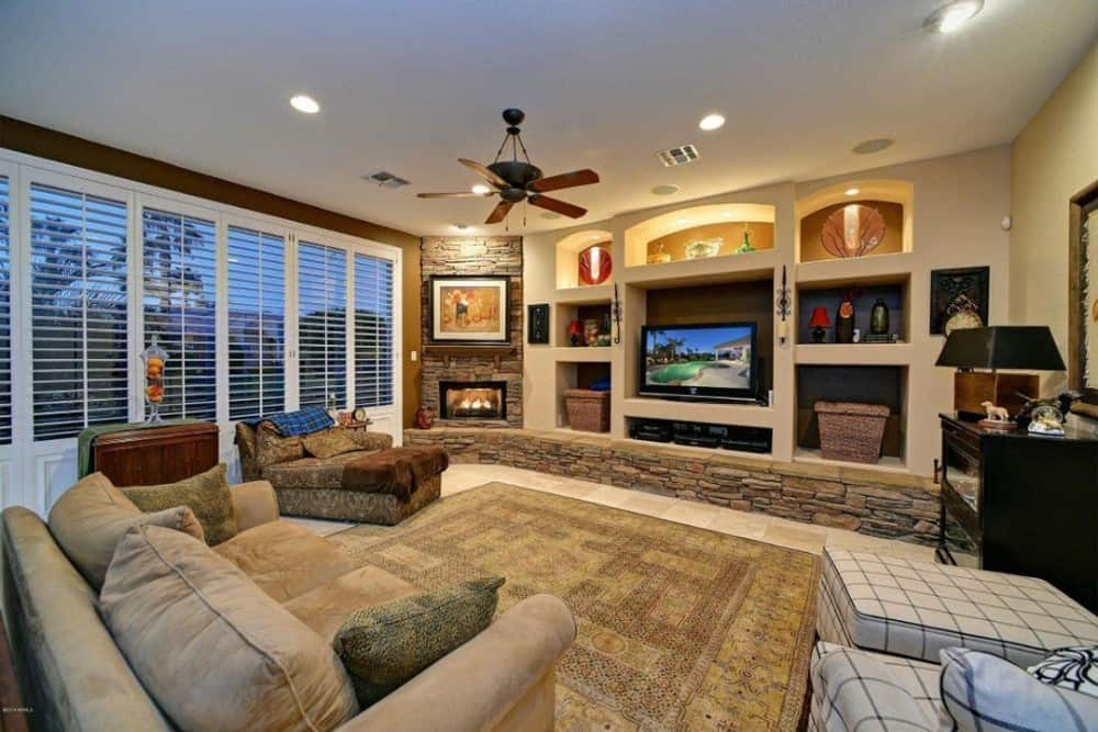 Family room with large comfy seats, a corner fireplace, a TV, and inset shelves filled with various decors.