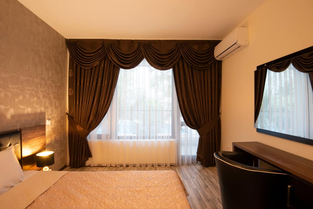 This is a luxurious bedroom that has a bed and study area and a curtained window on the far side with valance.