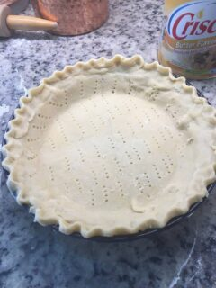 The pie crust on the pie pan is pricked with a fork.