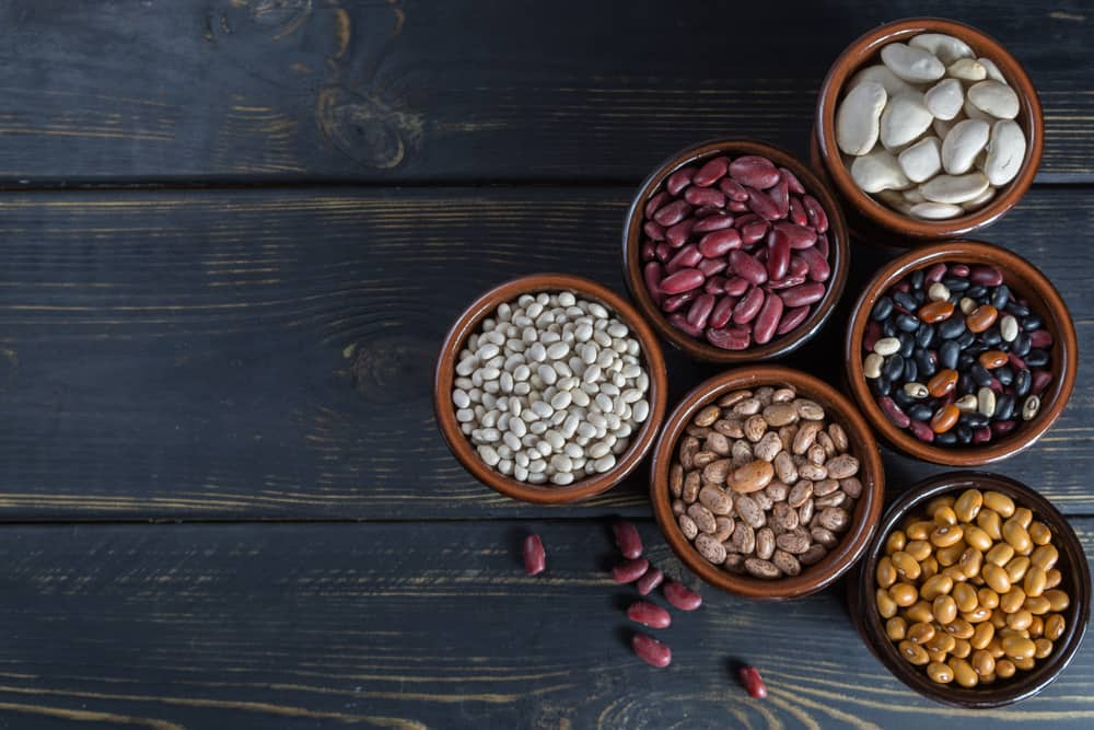 These are various types of beans in small bowls.