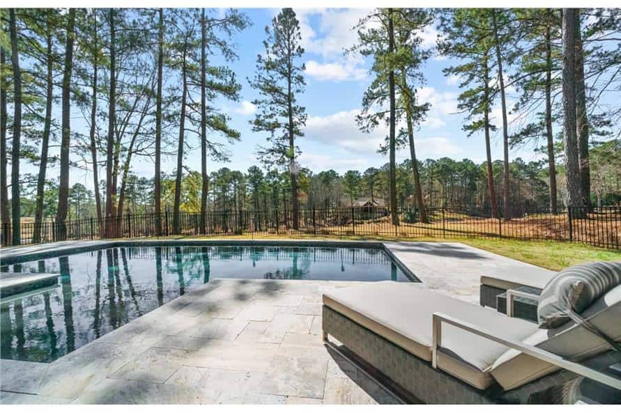 The pool with a cushioned lounger has a great view of the expansive surrounding.