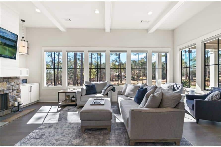 Keeping room with lots of fabric seats, stone fireplace, and surrounding windows that flood the room with fresh sunlight.
