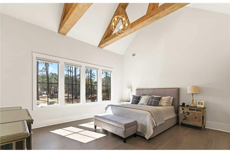 The primary bedroom has mirrored nightstands, a gray upholstered bed, and a matching ottoman under the cathedral ceiling with exposed trusses.