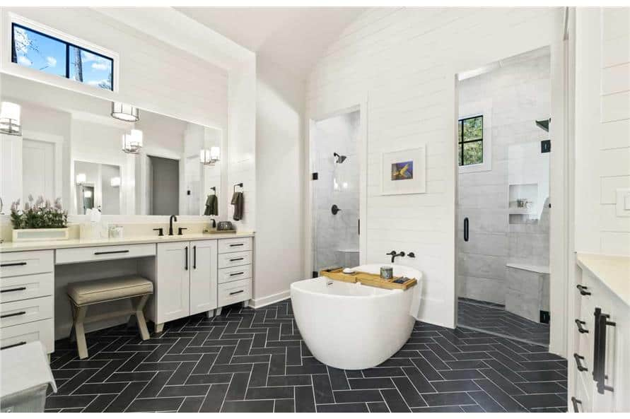 Primary bathroom with a large vanity, a freestanding tub, and a spacious walk-in shower with two glass doors and two showerheads.
