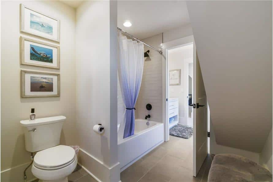 The bathroom includes a toilet area adorned with a trio of framed artworks.