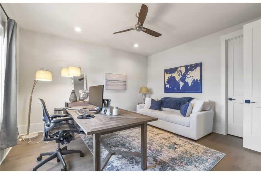 Home office with a white sectional, a swivel chair, and a wooden desk sitting on a distressed area rug.