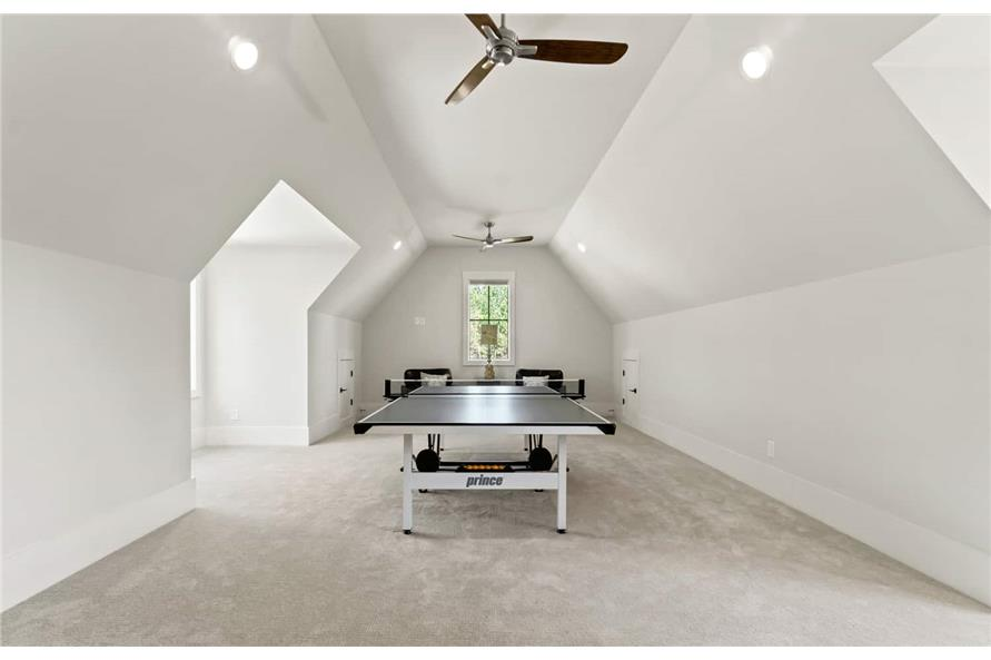 Bonus room with a pingpong table and ceiling fans mounted on the coved ceiling.