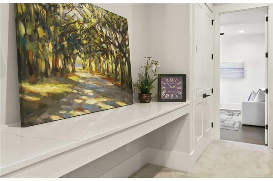 One side of the hall includes a storage closet and a built-in table topped with a large painting.