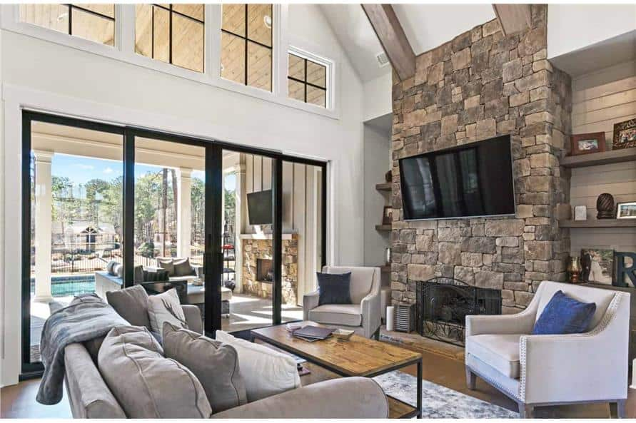 The living room has a high vaulted ceiling, gray seats, a stone fireplace, and sliding glass doors that lead to a covered porch.