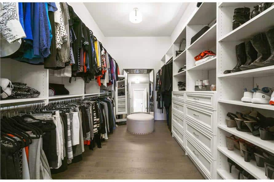 The primary walk-in closet is filled with white built-in shelves, a full-length mirror, and a round ottoman.