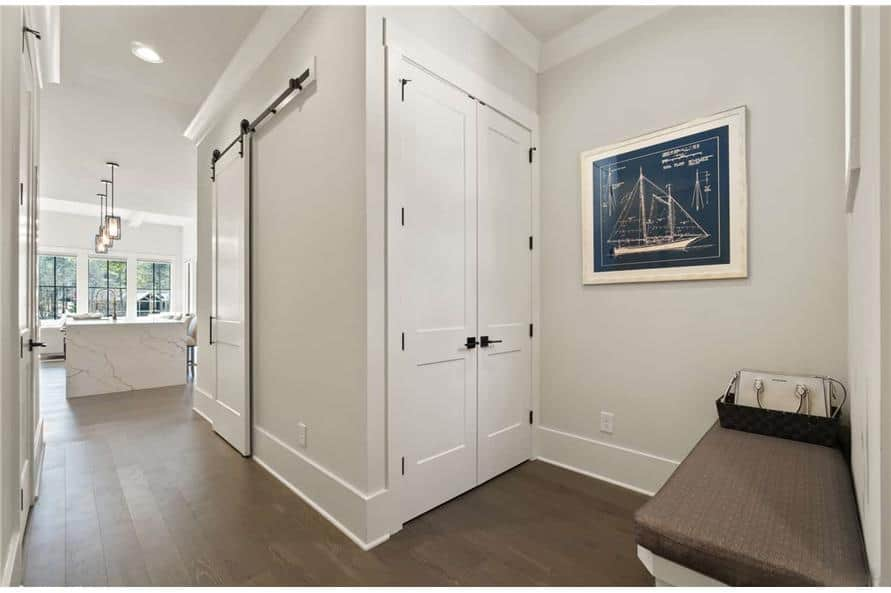 Mudroom off the kitchen with a cushioned bench and a storage closet concealed behind the double doors.