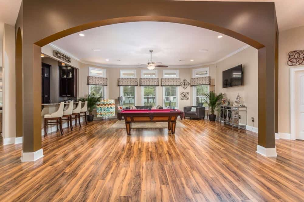 Large archways lead to the living room that's brightened by a bow window.