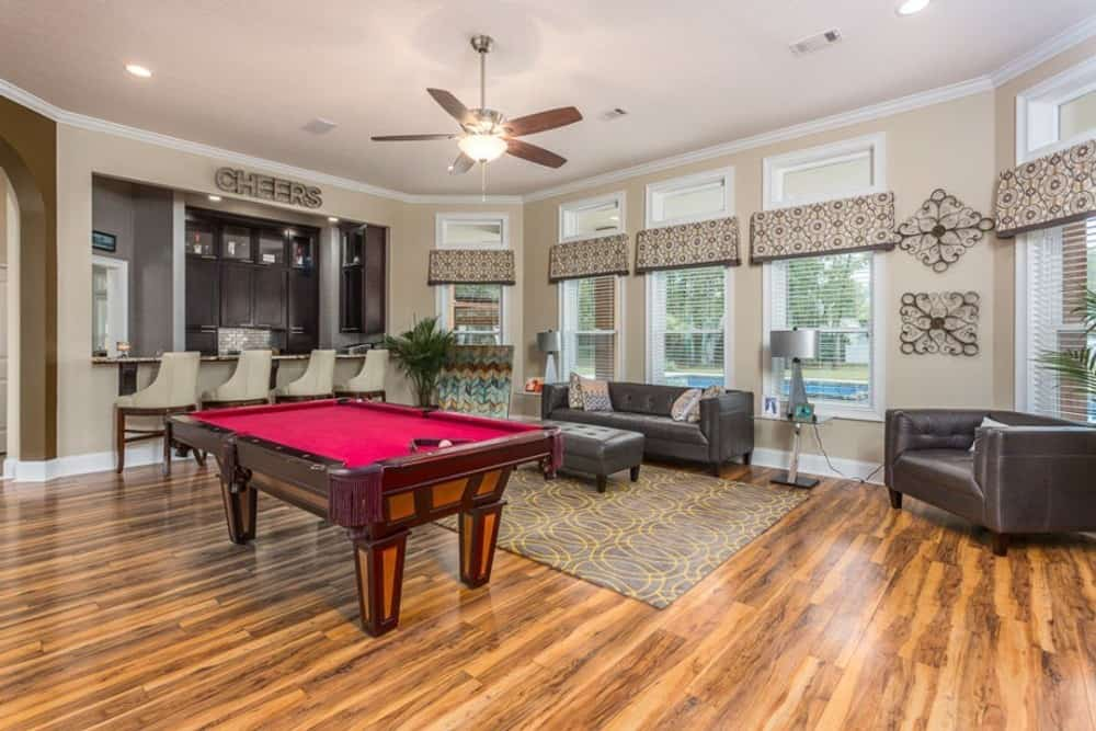 The living room offers a billiard table, a fun bar, and leather tufted seats paired with a matching ottoman.