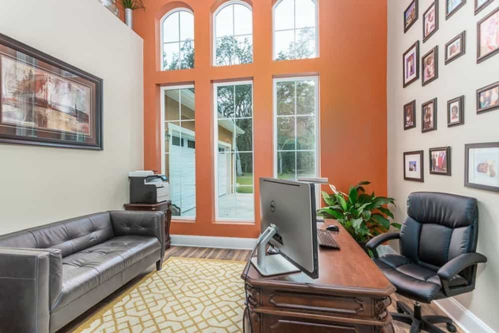 Study with leather sofa and a wooden desk. It is graced with a gallery wall and an orange accent wall fitted with tall windows.