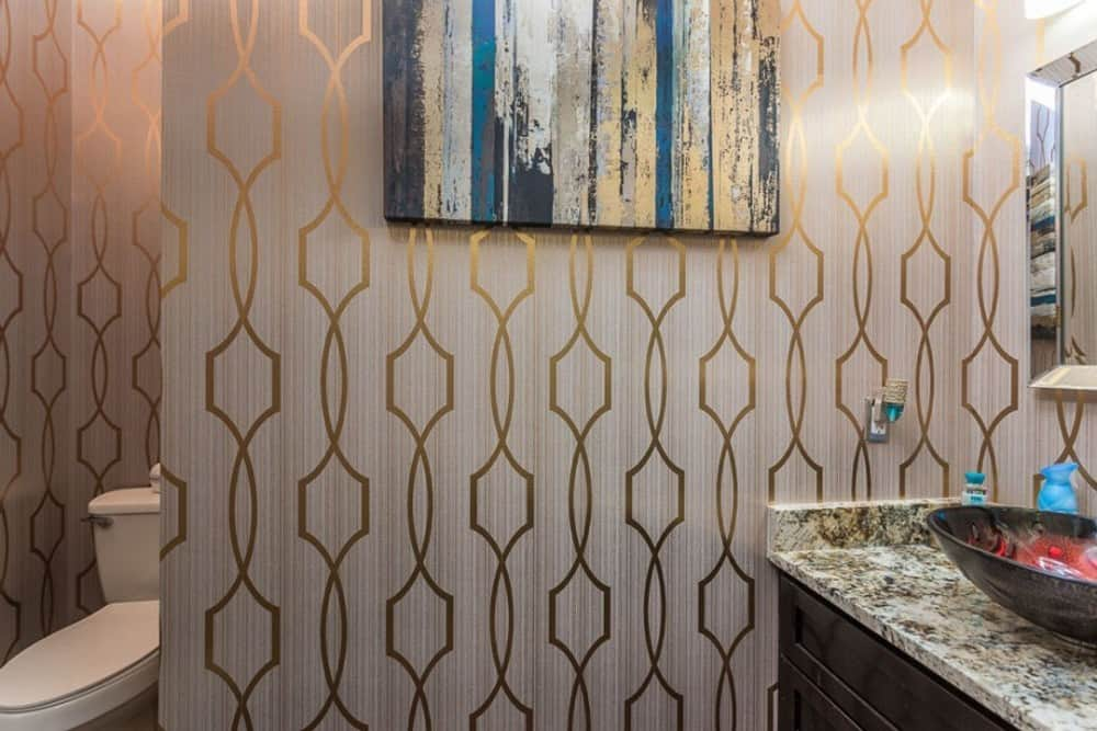 The primary bathroom has also a striking patterned wallpaper graced with an abstract painting.