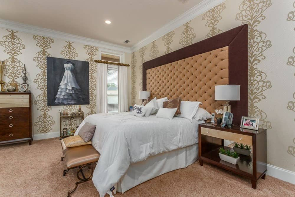 The primary bedroom features a patterned wallpaper, carpet flooring, and a skirted bed accentuated with a large, custom tufted headboard.