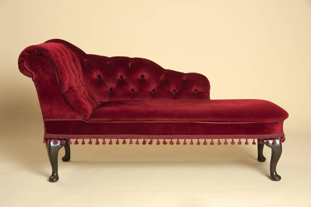 This is a dark red velvet tufted chaise lounge divan with dark wood legs.