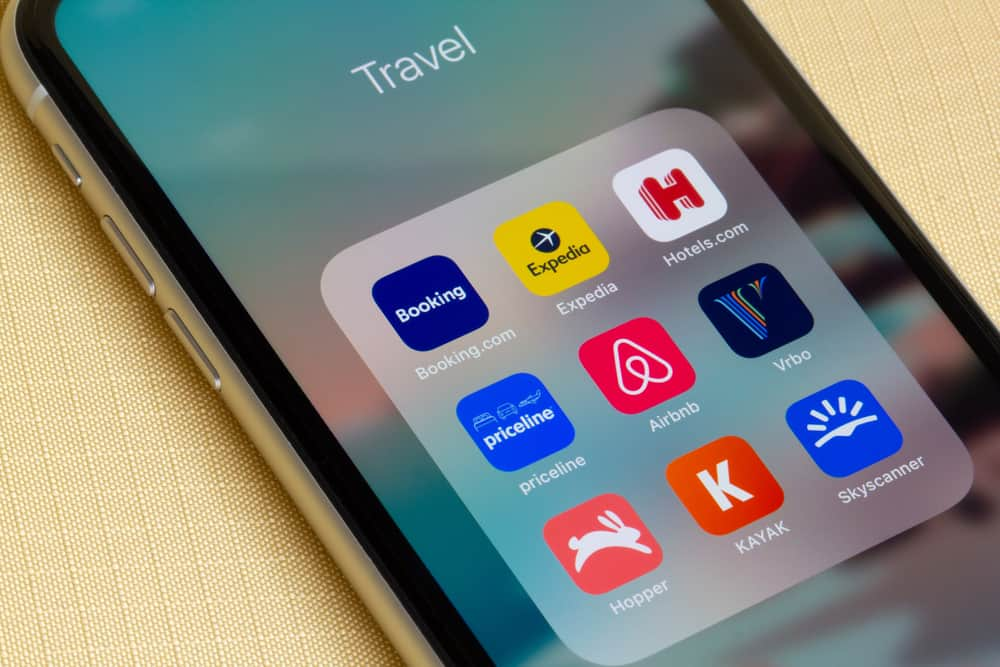 This is a close look at a mobile phone showcasing various travel apps including Airbnb and VRBO.