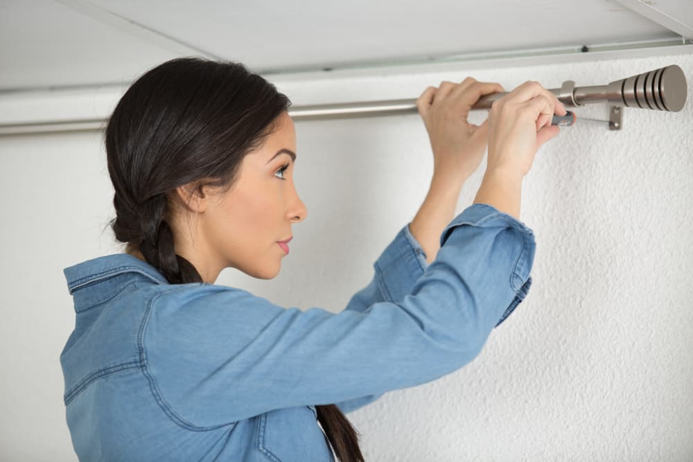 This is a woman installing the curtain rod and bracket on the wall.