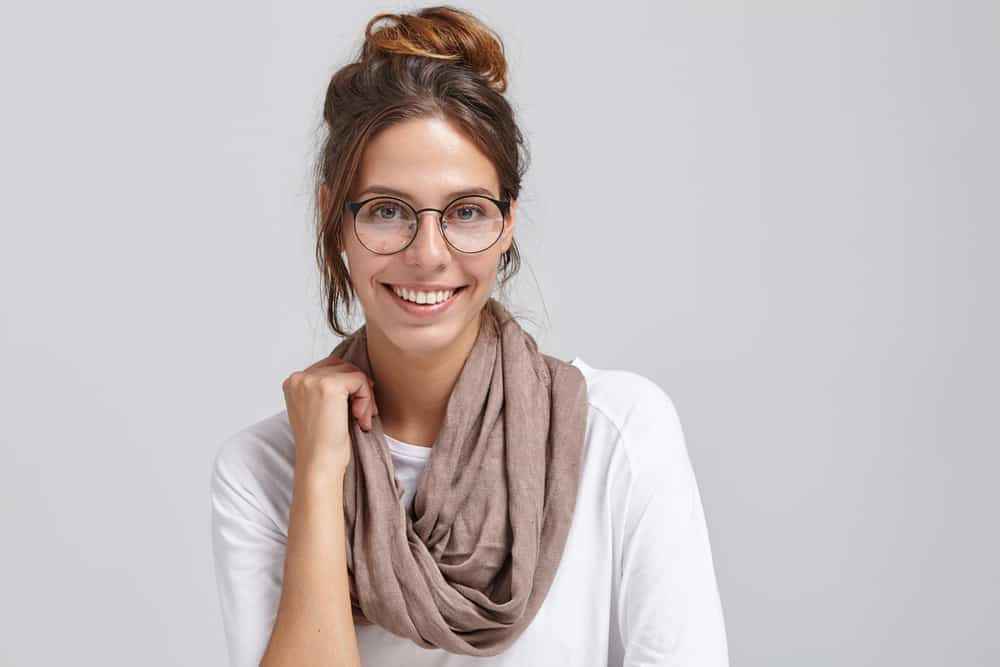 This is a woman wearing a white shirt, a pair of glasses and a beige basic scarf.
