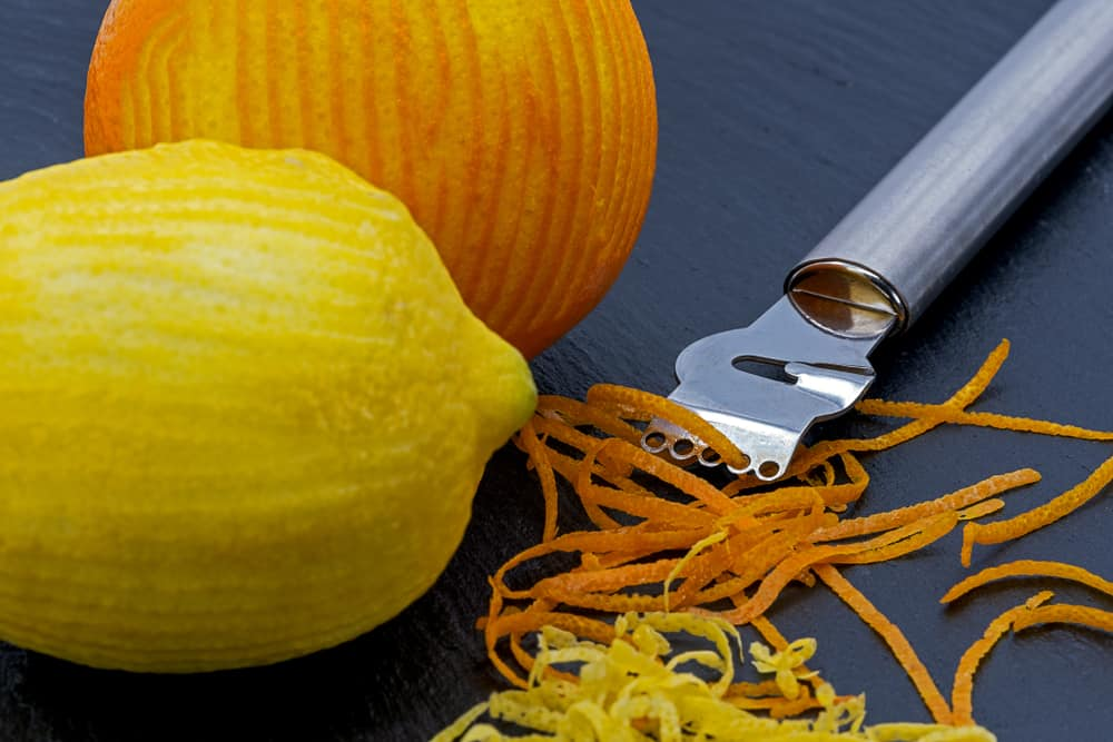 This is a close look at a a couple of citrus being zested with a special tool.