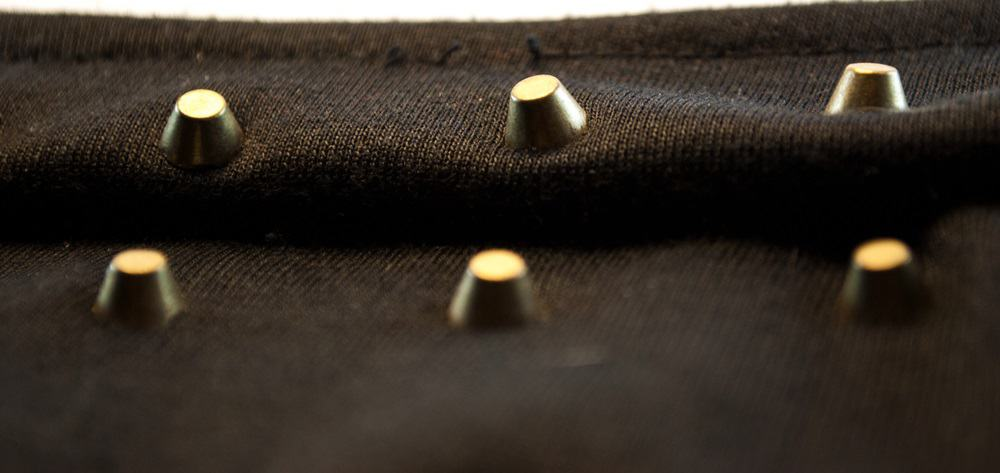 These are small spur grommets sewed onto the dark fabric.