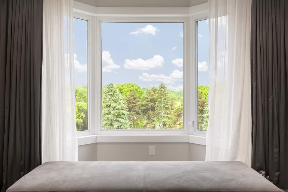 The bedroom bay window has a layer of sheer curtains and a layer of blackout curtains.