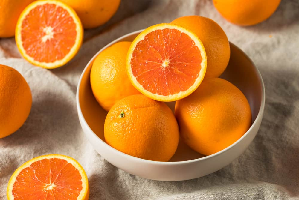 Pieces of ripe and sliced caracara oranges on a bowl.