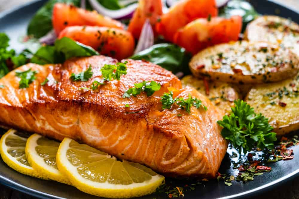 A close look at roasted salmon with a side of vegetables.