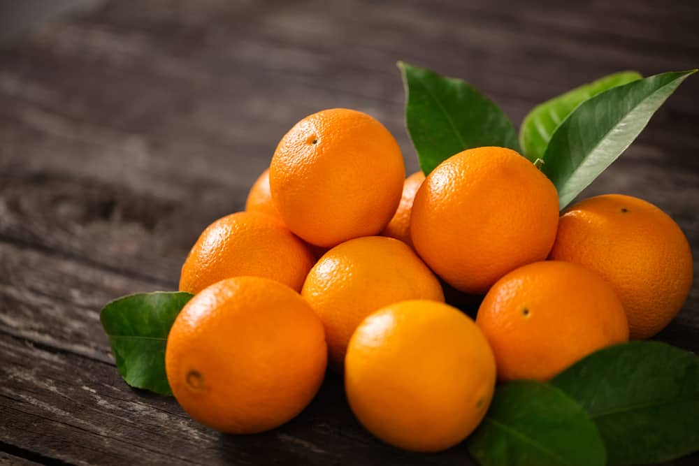 These are a bunch of ripe oranges on a wooden table.