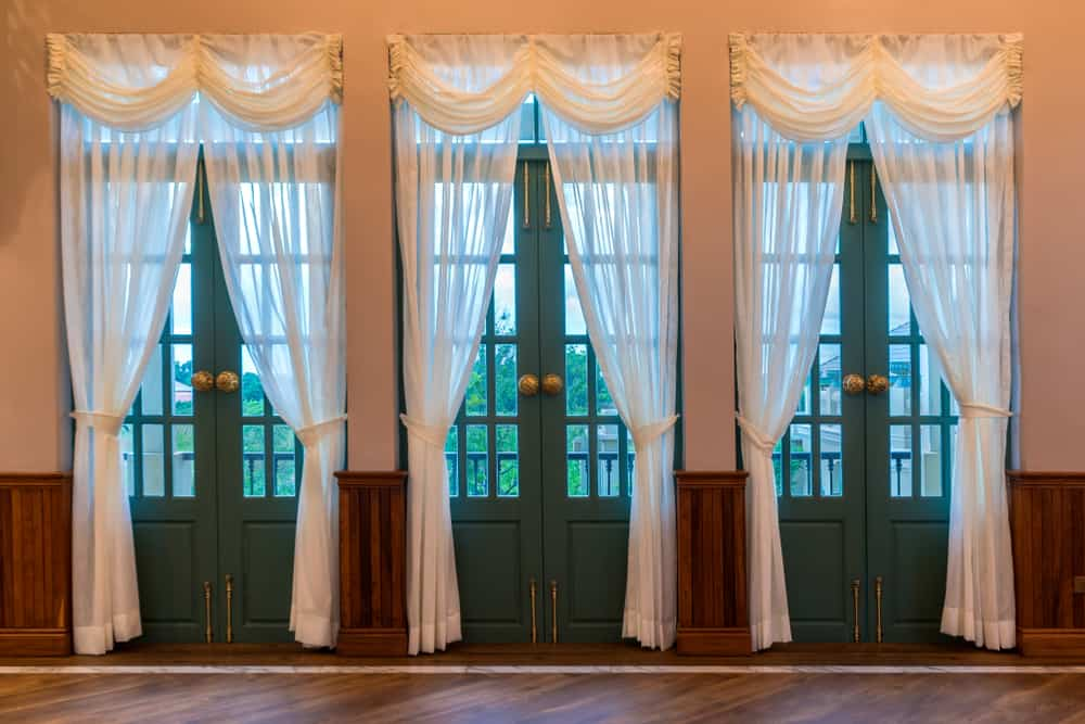 These are French doors complemented by their white sheer curtains.