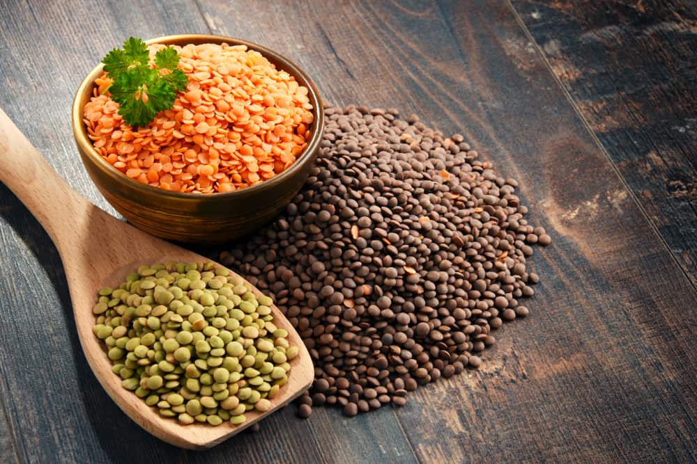 A bunch of red, green and brown lentils on a wooden table.