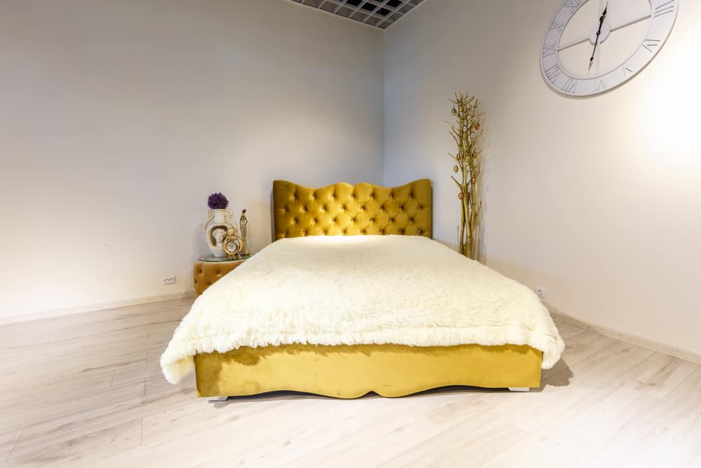 This is a yellow tufted chesterfield style bed at the corner.