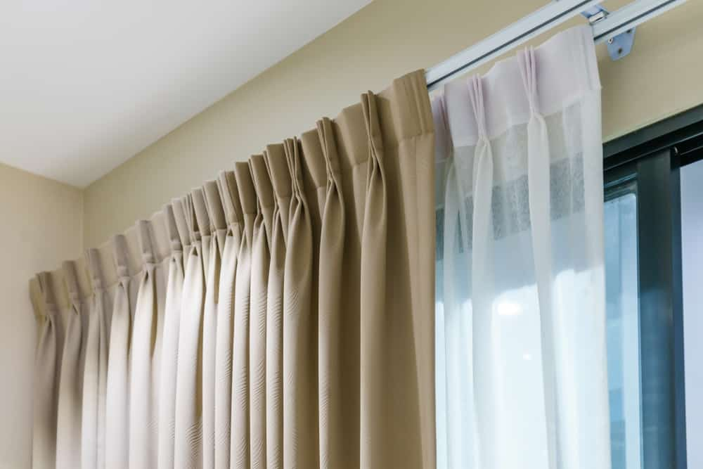 These are pleated beige and white sheer curtains with grommets and eyelets.