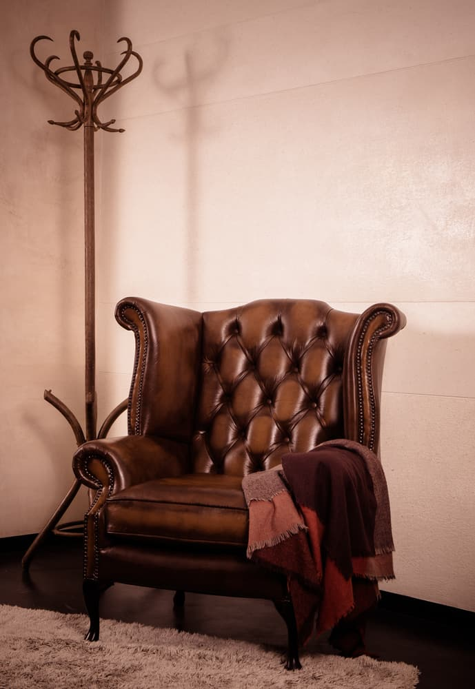 This is a brown leather Chesterfield Queen Anne Armchair beside a coat rack.