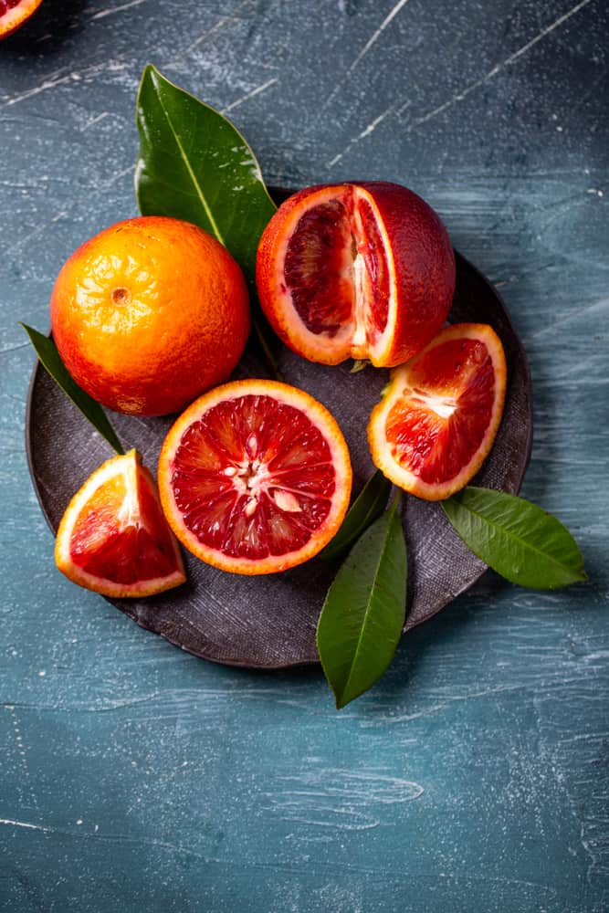 These are blood oranges with slices on a dark plate.