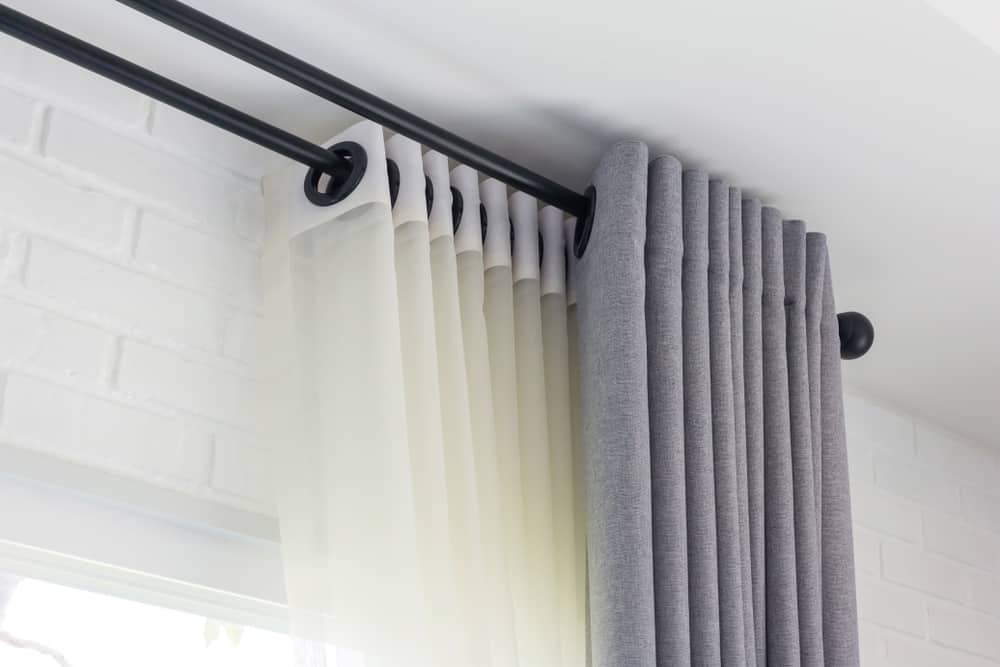 These are white sheer and gray blackout curtains mounted with black rods and black eyelets.