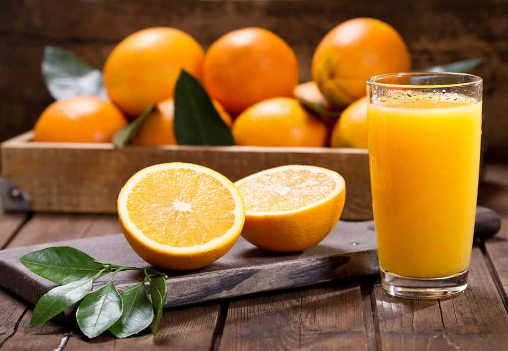 A glass of fresh orange juice with ripe oranges on the side.